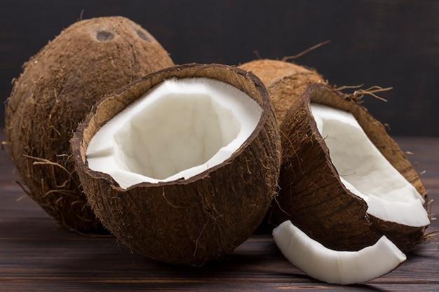 Coco picado ao meio coco em fundo escuro de madeira.
