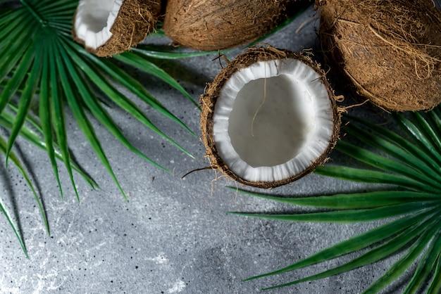 Coco picado maduro em um fundo de pedra cinza. lugar para o seu texto