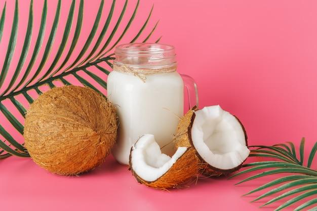 Coco rachado e leite de coco em vidro rosa brilhante