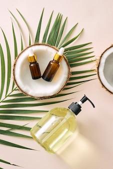 Coco rachado e uma garrafa de óleo sobre a mesa - conceito de spa, cuidados com a pele, cabelo e relaxamento