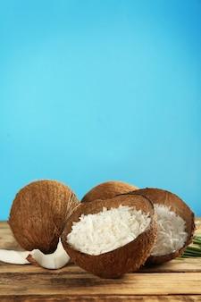 Coco ralado com casca e nozes inteiras na mesa de madeira