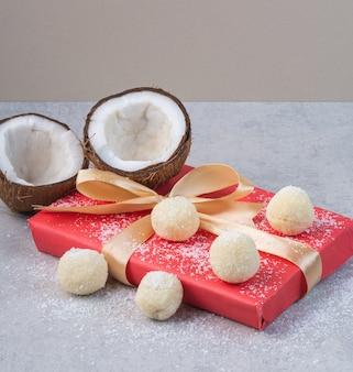 Cocos, bolinhos e caixa para presente, sobre a mesa de mármore.