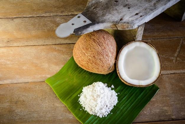 Cocos e flocos de coco na folha de bananeira e ralador de coco
