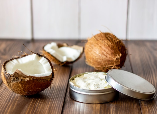 Cocos e óleo de coco em uma panela de metal. fundo de madeira