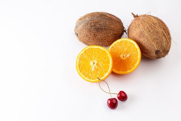 Cocos frescos de vista frontal junto com fatias de laranja no branco