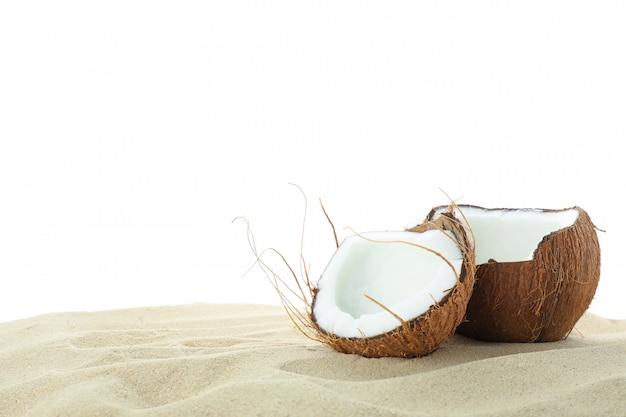 Cocos na areia clara do mar, isolada no fundo branco. férias de verão