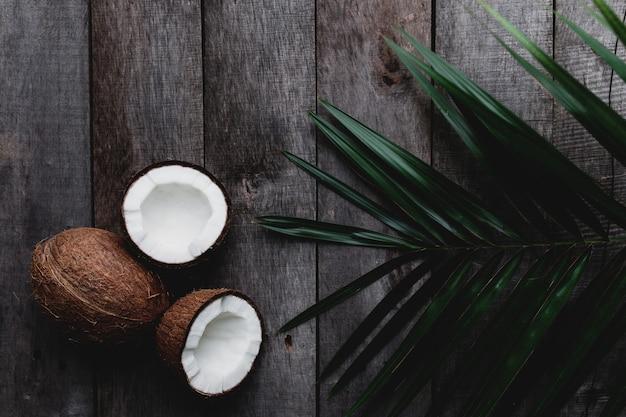 Cocos quebrados em fundo cinza de madeira com folha de palmeira. polpa de coco branca. foto de alta qualidade