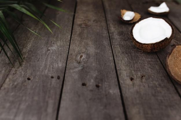 Cocos quebrados em fundo cinza de madeira com folha de palmeira. polpa de coco branca.