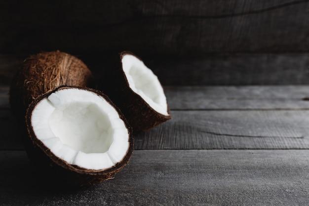 Cocos quebrados em fundo cinza de madeira. polpa de coco branca. foto de alta qualidade