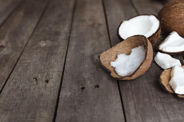 Cocos quebrados em fundo cinza de madeira. polpa de coco branca.