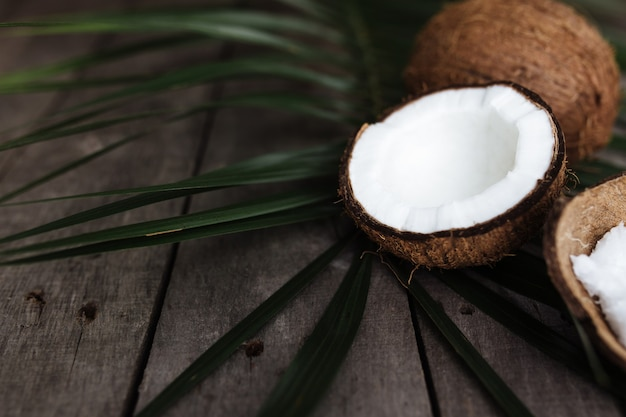 Cocos quebrados na superfície de madeira cinza com folha de palmeira. polpa de coco branca.