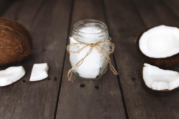Cocos quebrados na superfície de madeira cinza com frasco de óleo de coco virgem extra orgânico cru. polpa de coco branca.