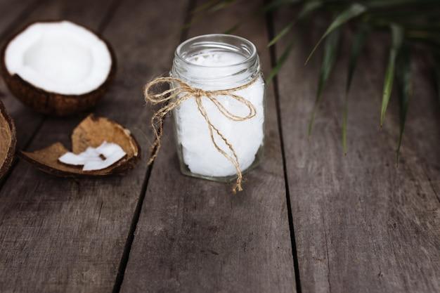 Cocos quebrados na superfície de madeira cinza com um frasco de óleo de coco virgem extra orgânico cru e folha de palmeira. polpa de coco branca.