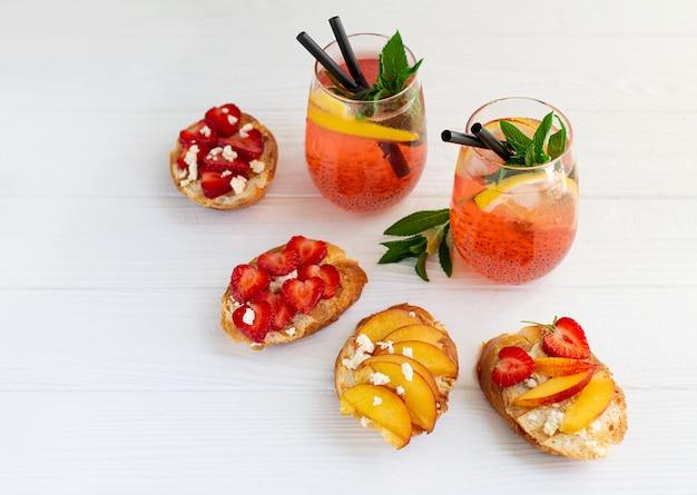 Coctails coloridos e brindes de frutas na mesa de madeira branca