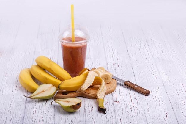 Cocto de desintoxicação vermelha com bananas na tábua de cortar está na mesa branca