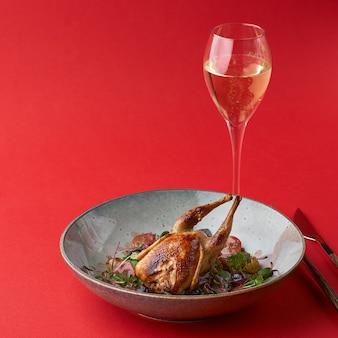Codorna assada e legumes frescos em um prato e uma taça de champanhe
