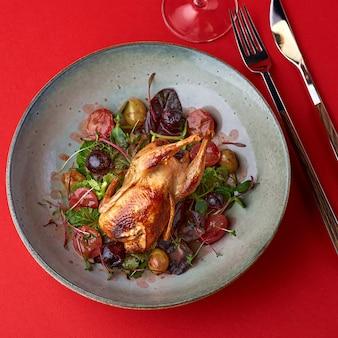 Codorna assada e legumes frescos em um prato