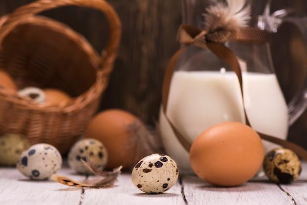 Codorna crua fresca e ovos de galinha, jarra de leite
