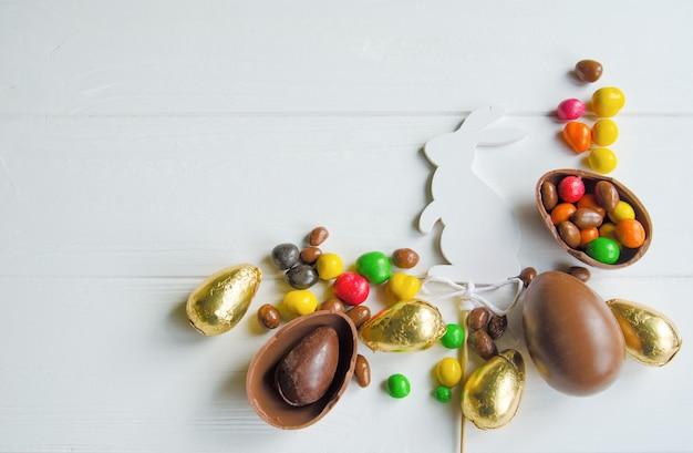 Coelhinho da páscoa branco com ovos de chocolate e doces em branco de madeira