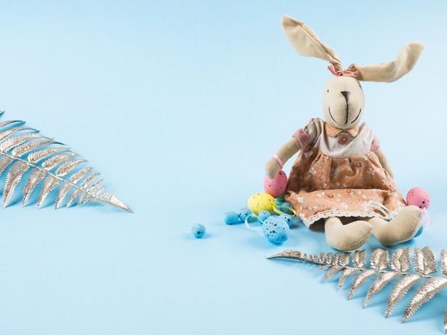 Coelhinho da páscoa com ovos coloridos no pano de fundo azul