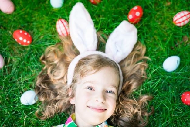 Coelhinho da páscoa. criança se divertindo ao ar livre. criança brincando com ovos na grama verde. conceito de férias de primavera
