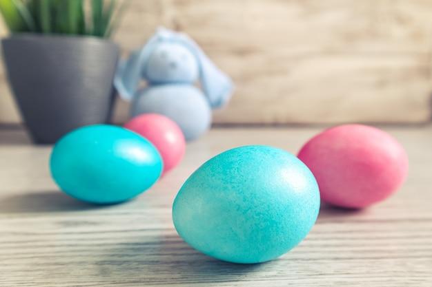 Coelhinho da páscoa de brinquedo e ovos pintados em uma mesa de madeira. decorações de páscoa, símbolo do feriado. foco seletivo em primeiro plano.