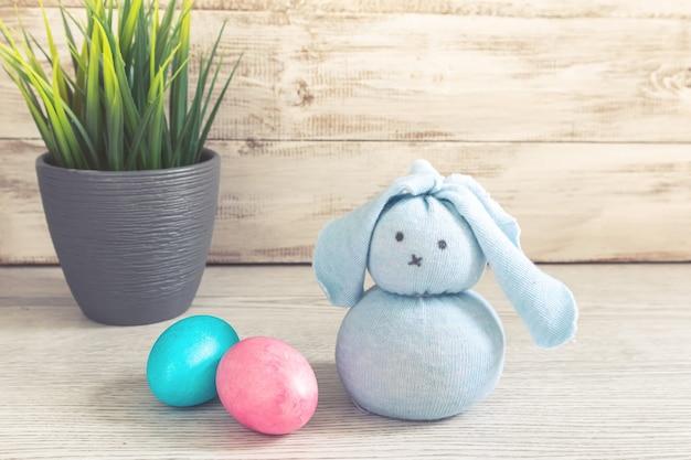 Coelhinho da páscoa de brinquedo e ovos pintados em uma mesa de madeira. decorações de páscoa, símbolo do feriado.
