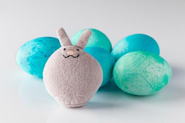 Coelhinho da páscoa de brinquedo fofo e ovos pintados de azul com penas
