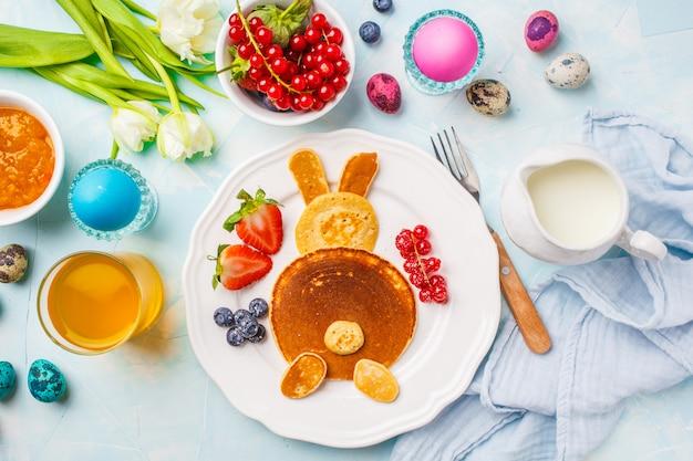 Coelhinho da páscoa de panquecas com bagas. tabela de café da manhã de páscoa. fundo azul, vista de cima.