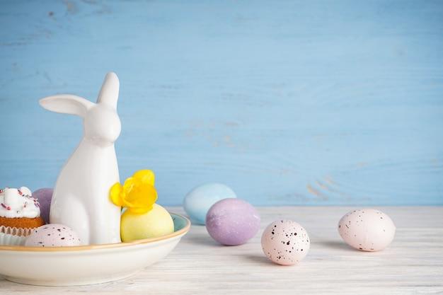 Coelhinho da páscoa e ovos com flores em um fundo de madeira