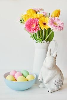 Coelhinho da páscoa e ovos da páscoa na mesa da cozinha. coelho branco sentado na mesa com buquê de tulipas e cume e ovos coloridos. decoração de páscoa com coelho e ovos. modelo de cartão de páscoa