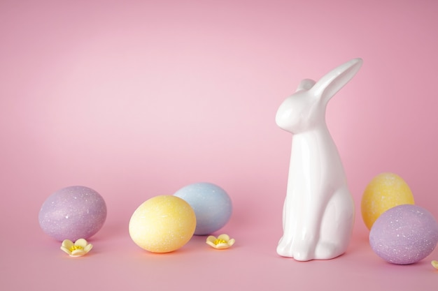 Coelhinho da páscoa e ovos de páscoa coloridos em fundo rosa. lugar para texto. conceito de feliz páscoa.