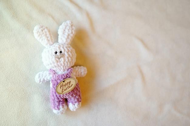 Coelhinho da páscoa na luz com espaço da cópia. brinquedo branco da criança do bebê. tradição, feliz feriado de páscoa