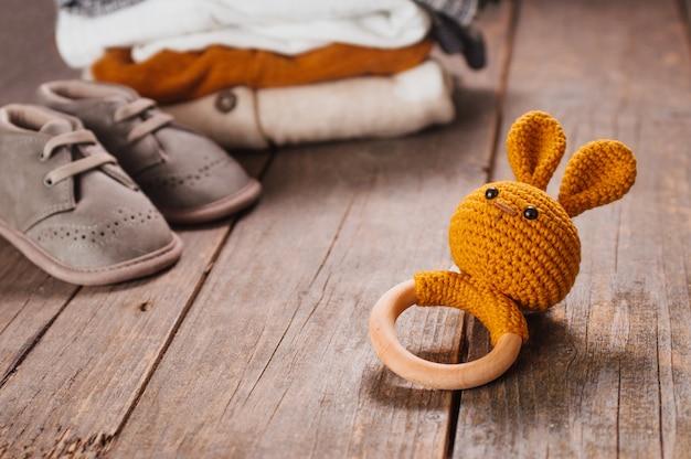 Coelhinho de brinquedo de madeira perto de botinhas e roupas de bebê