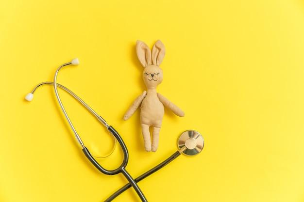 Coelhinho de brinquedo e estetoscópio de equipamentos de remédios isolado na mesa amarela