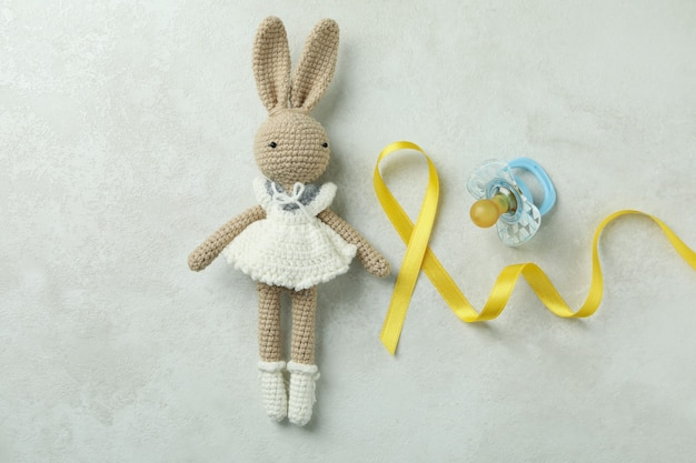 Coelhinho de brinquedo, fita de conscientização do câncer infantil e chupeta em branco