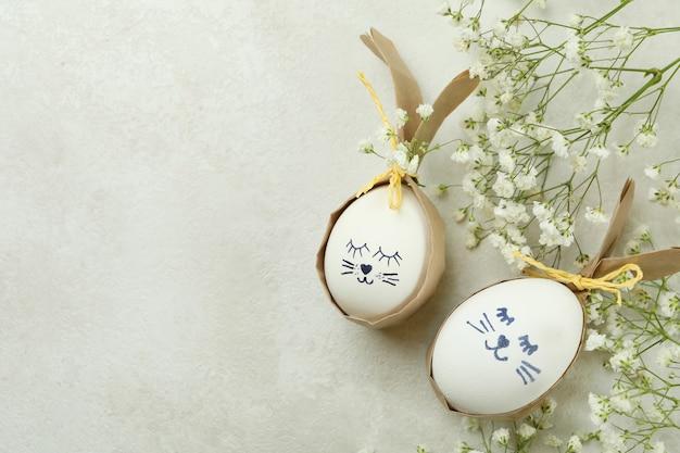Coelhinhos da páscoa feitos de ovos e flores de gipsófila em um plano de fundo texturizado branco
