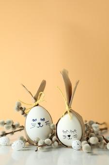 Coelhinhos da páscoa feitos de ovos, ovos de codorna e amentilhos contra um fundo bege
