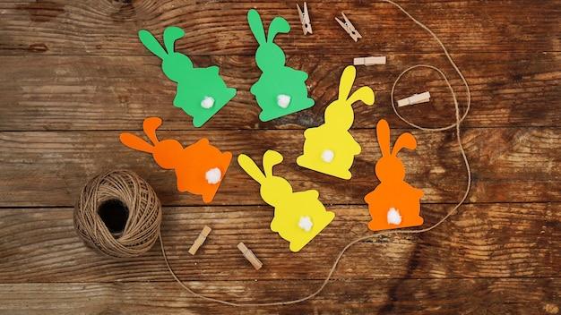 Coelhinhos da páscoa feitos de papel em uma superfície de madeira