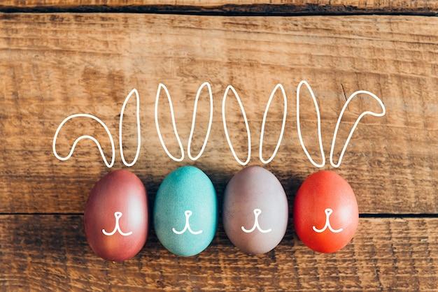 Coelhinhos da páscoa. vista superior de ovos de páscoa coloridos em uma mesa rústica de madeira em uma fileira
