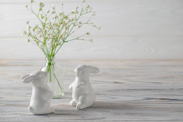 Coelhinhos de cerâmicos brancos na mesa de madeira branca com flores frescas da primavera branca