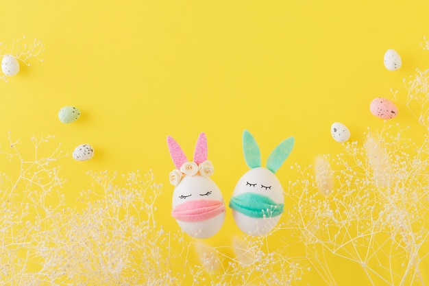 Coelhinhos de ovos de páscoa em máscaras protetoras em uma parede amarela. conceito de pandemia de coronavírus.
