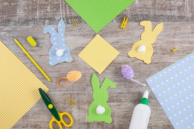 Coelhinhos de papel de páscoa coloridos com cauda na mesa de madeira