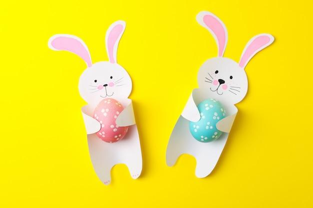 Coelhinhos decorativos e ovos de páscoa na superfície amarela