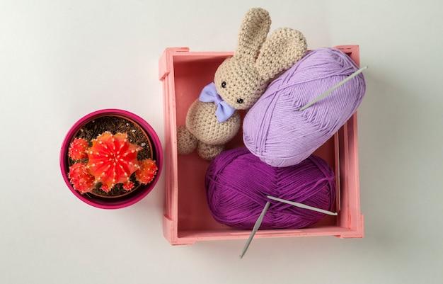 Coelho amigurumi com olhos pretos e gravata borboleta, cacto, caixa de lã e ganchos de crochê
