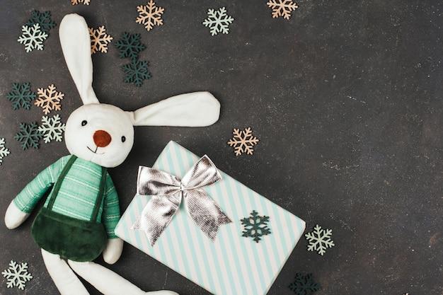 Coelho de brinquedo branco, caixa de presente com laço e flocos de neve de madeira sobre um fundo cinza escuro.