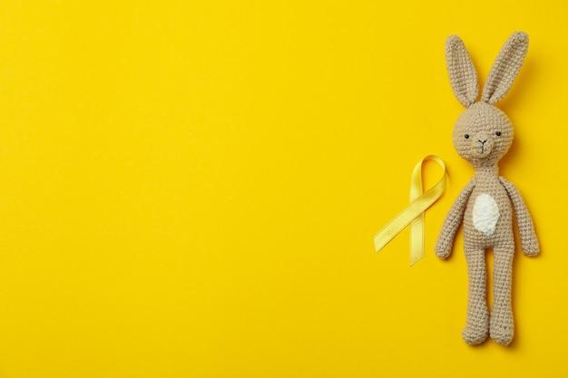 Coelho de brinquedo e fita de conscientização do câncer infantil em fundo amarelo