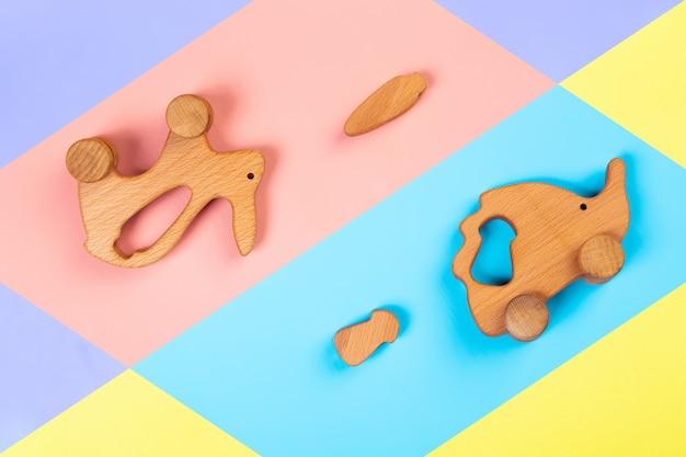 Coelho de brinquedos de madeira com cenoura, ouriço com cogumelos em um fundo geométrico vibrante multicolorido isolado.