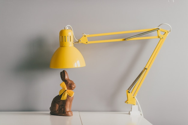 Coelho de chocolate com sentado na mesa sob a lâmpada amarela.