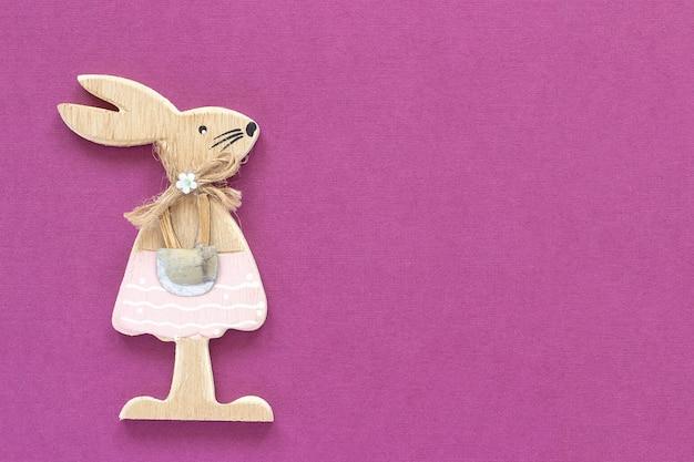 Coelho de coelho estatueta de madeira no fundo de papel roxo cartão de dia dos namorados conceito ou cartão de feliz páscoa vista superior
